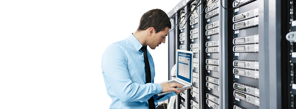 Man holding laptop inside a Data Centre