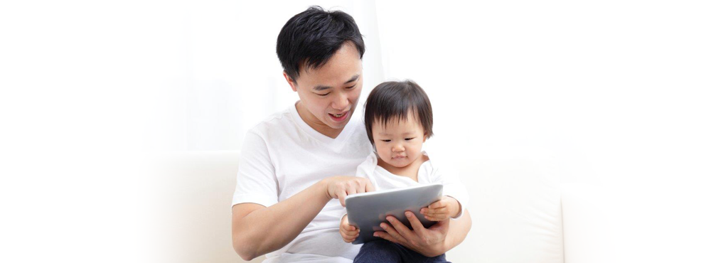 Dad and child on couch with a tablet