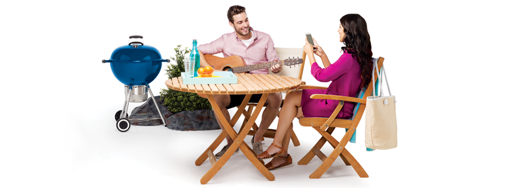Man and woman sitting at table outside with BBQ.