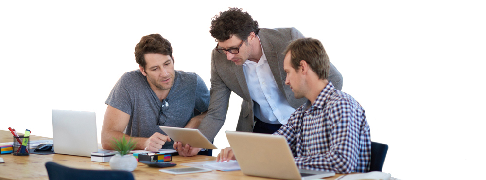 Three coworkers looking at computers together