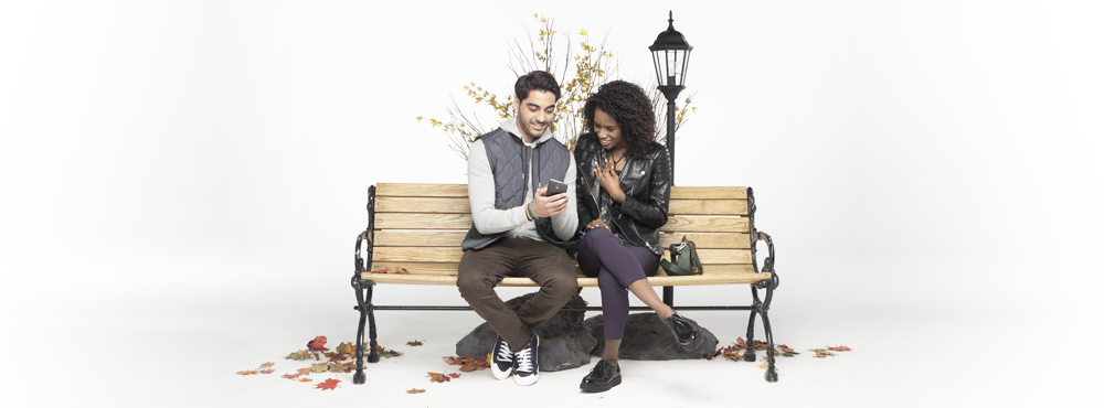 A young man & woman sitting on a bench looking at a smartphone