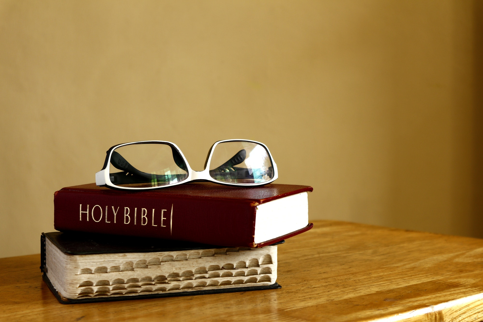 Holy Bibles and eyeglasses on a table