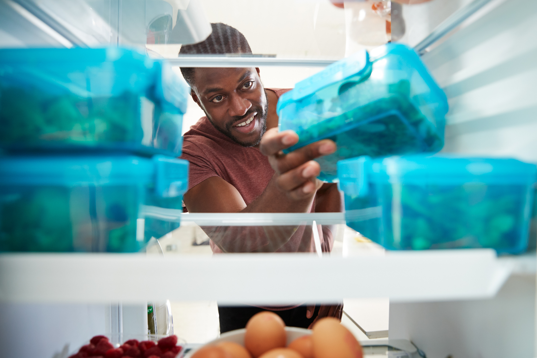 Man pulling prepped meals out of the fridge