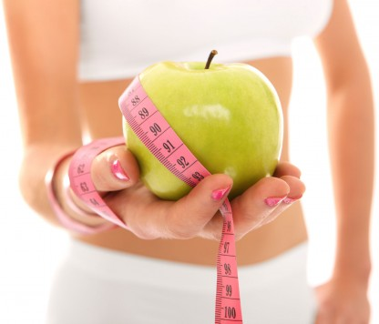Woman holding out an apple to illustrate the benefits of exercise on digestive health