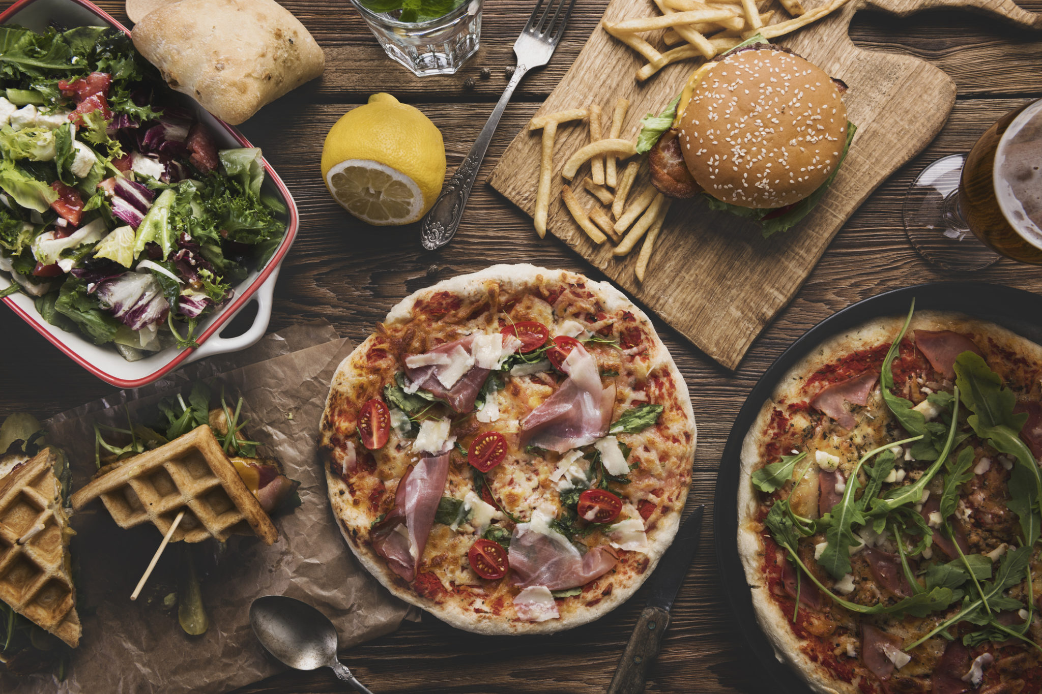 Fast food on old wooden background.