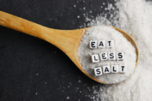 Eat less salt advice written with plastic letter beads on granulated salt