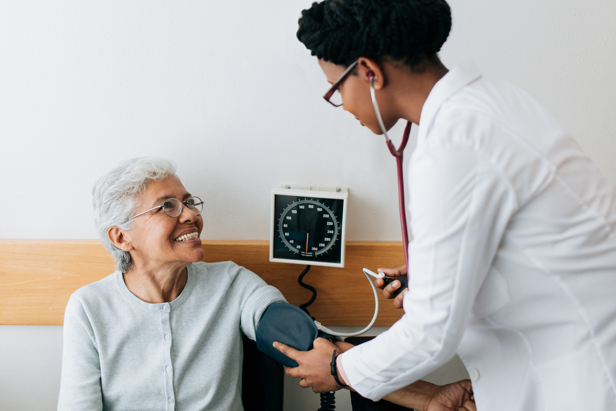 Female doctor checking blood pressure to senior patient