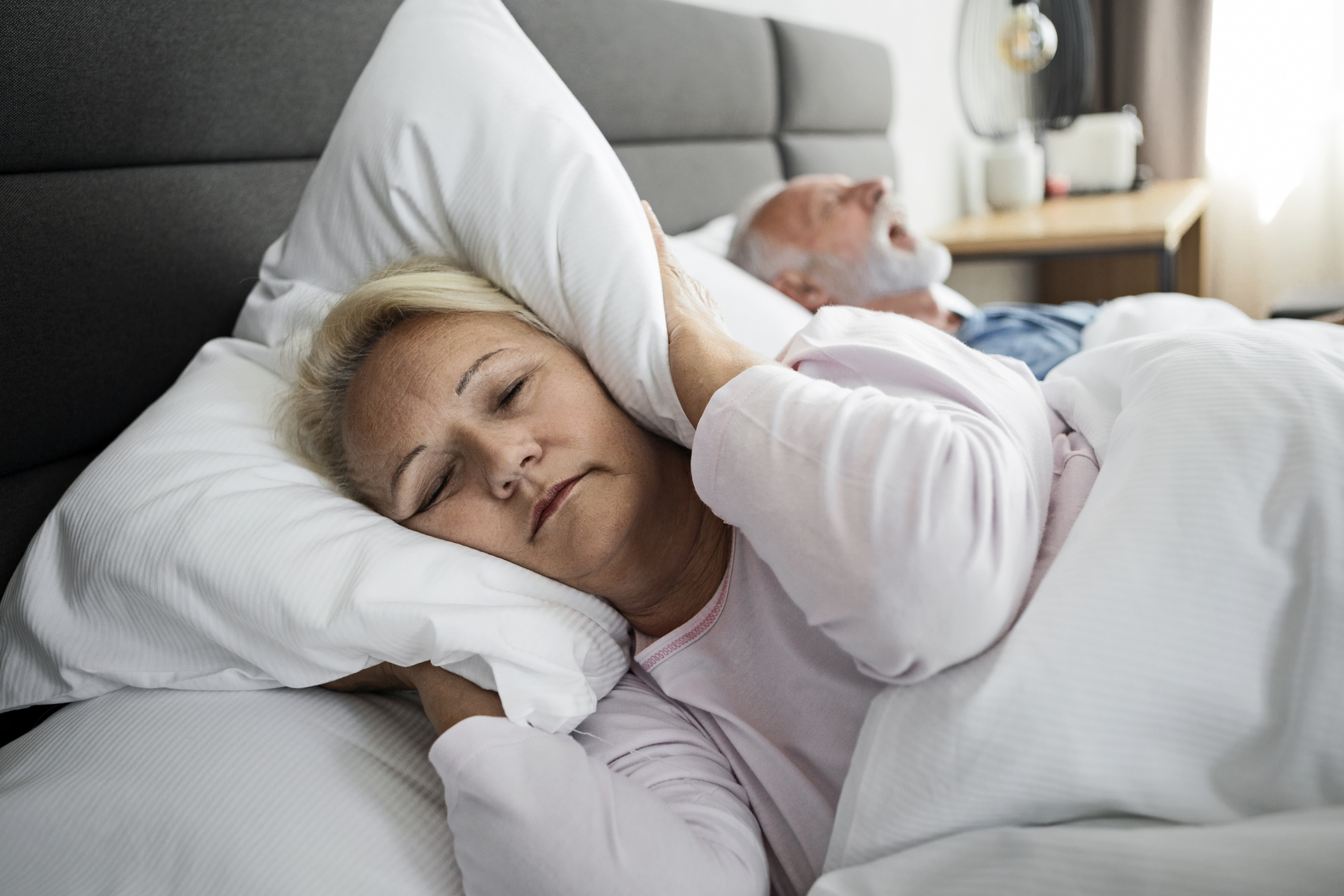 Wife blocking ears with pillow while husband snoring in sleep