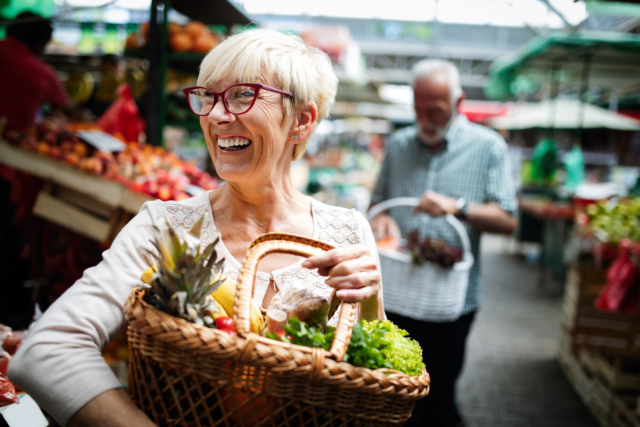 Senior couple buying fresh vegetables and fruits together.