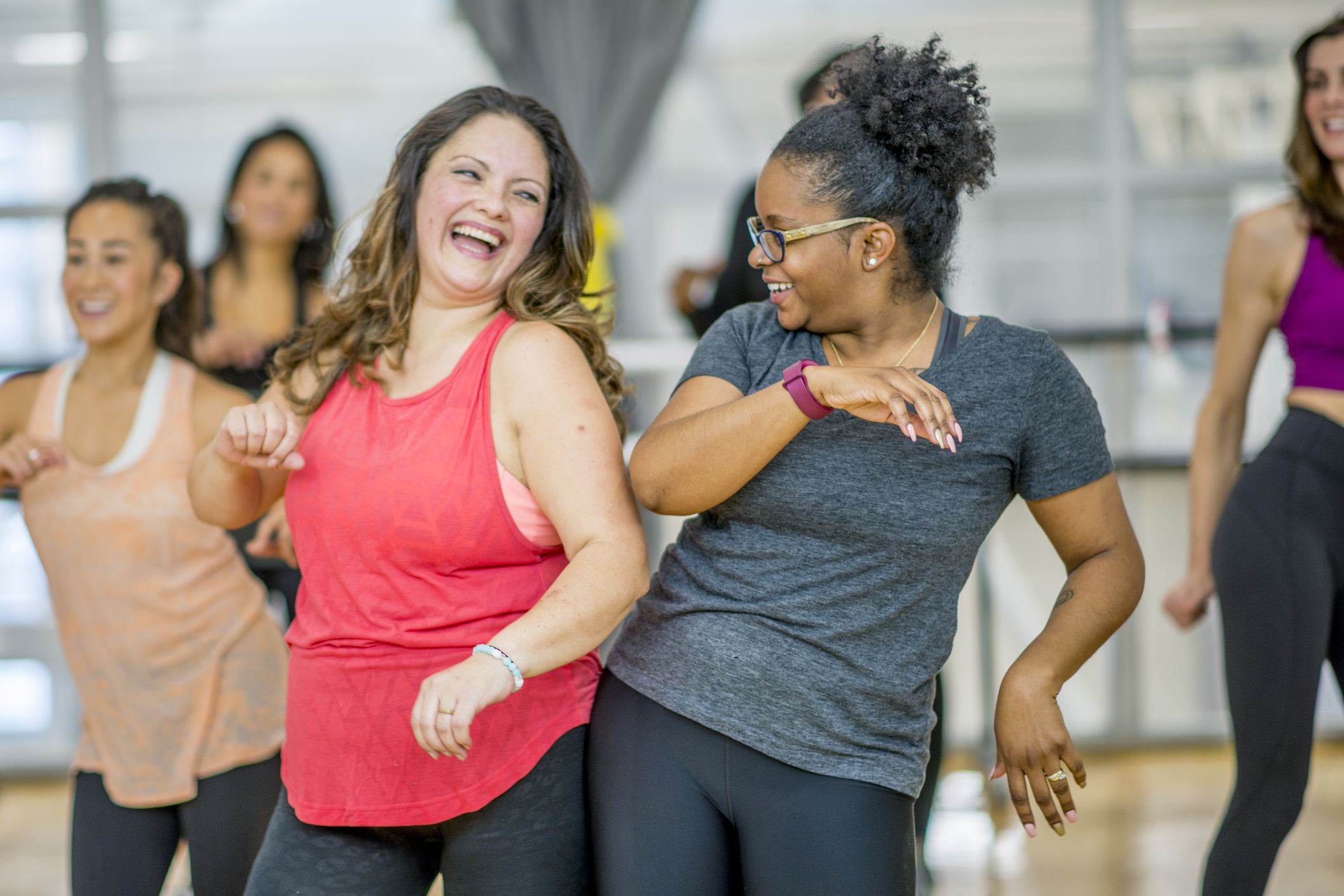 Two woman dancing in an exercise class to reduce their risk of CAD