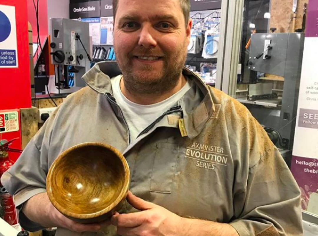 Chris grins as he shows a smooth, shiny light brown wooden bowl fresh off the turning board.