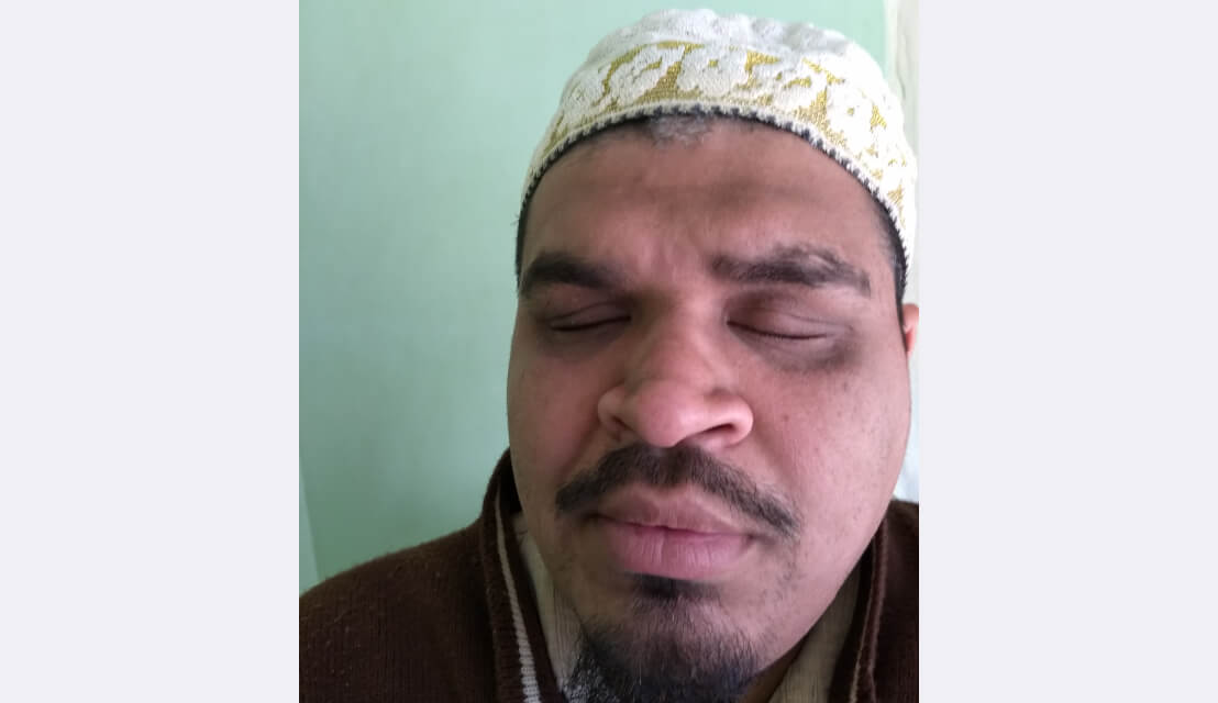A profile picture of Dr. Yusuf. He's wearing a white hat with golden embroidery and a dark, red sweater.