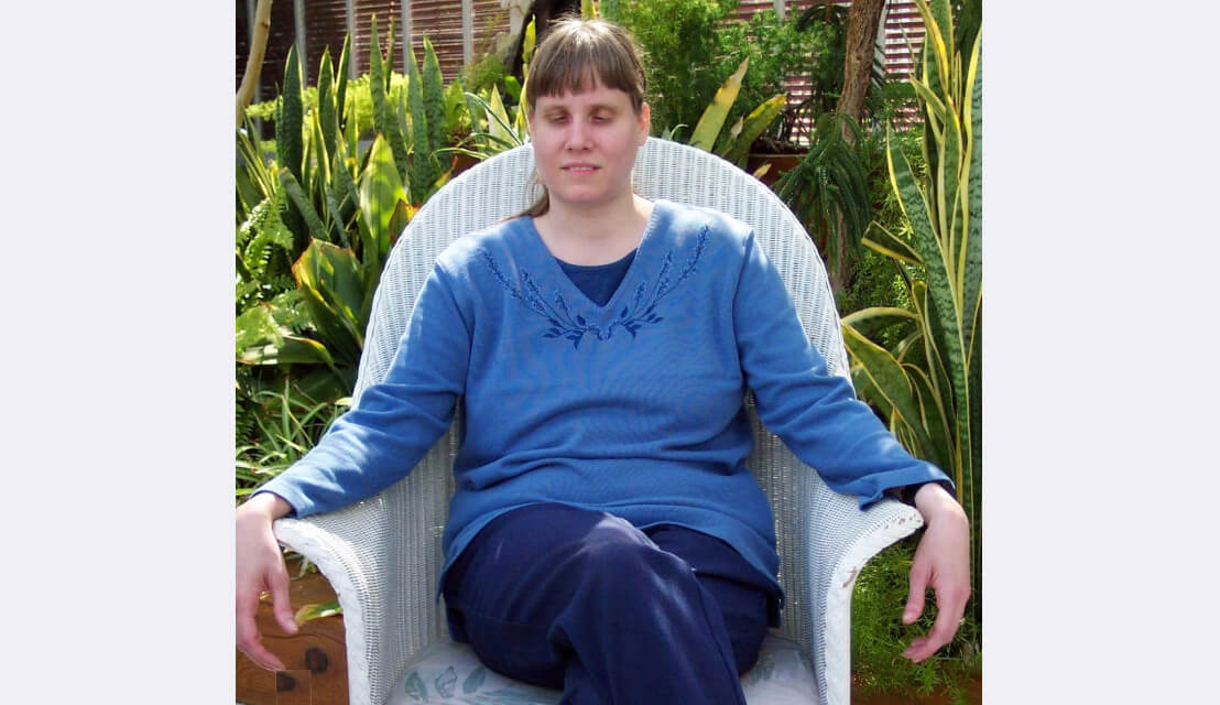 Konnie is seated on a wicker chair in a garden. She wears a blue sweater and jeans, draping her arms alongside the armrests.