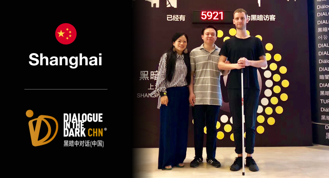 From left to right, Shiyin Cai and Zhang Jie from Dialogue in the Dark Shanghai beside Jozef Simo, Be My Eyes Team designer. The group stands smiling at the entrance of DiD in front of a braille-inspired logo.