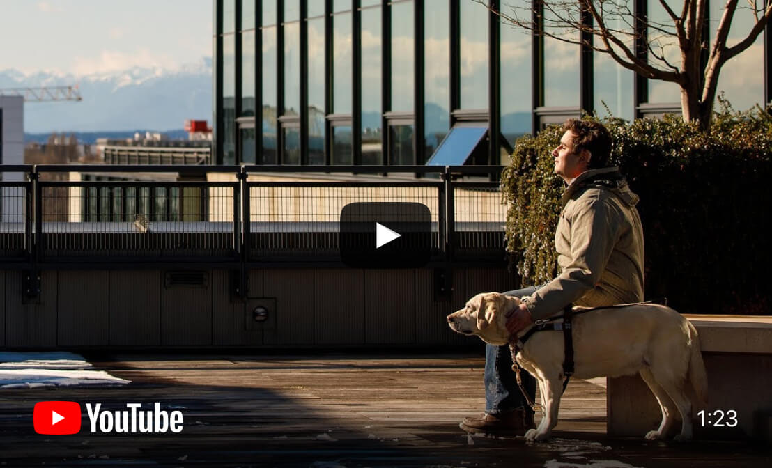 YouTube video cover image depicts Michael, seated on a bench beside his guide dog, enjoying the sunshine with snow-capped mountains in the distant background.