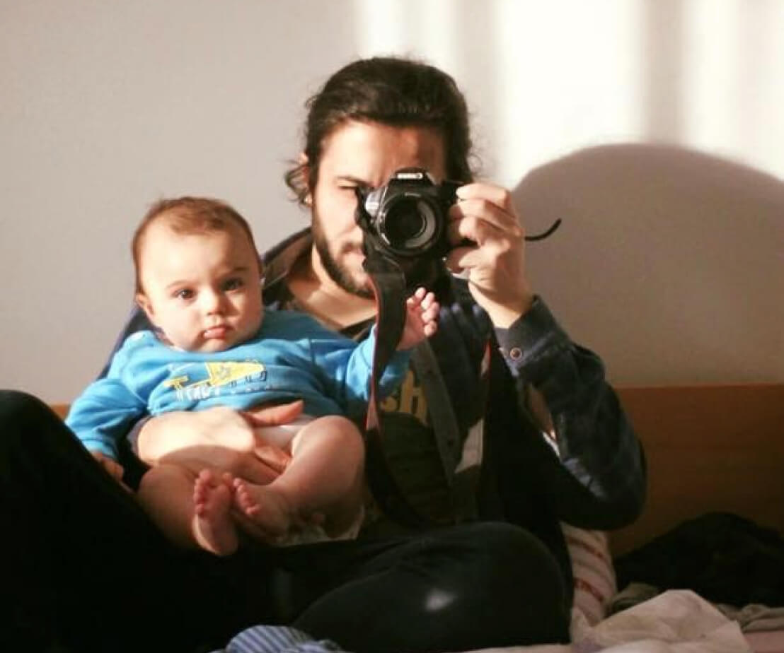 Leo snaps a shot of himself and his son in the reflection of a mirror. His infant son rests in his lap.