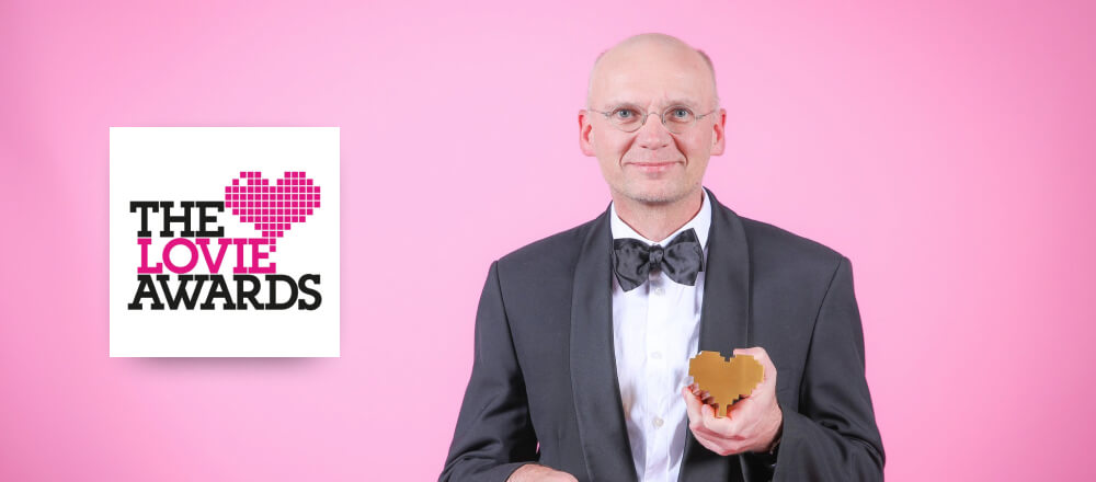 Be My Eyes founder, Hans Jørgen Wiberg, posing in front of a pink backdrop, characteristic for the Lovie Awards, while holding his heart shaped award.