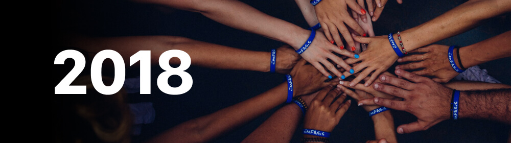 """Hands of people with blue bracelets put together with """"2018"""" written across."""