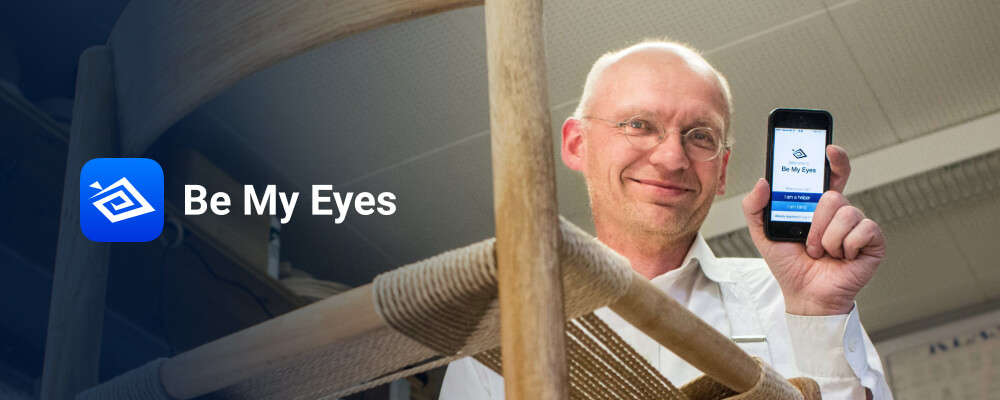 The Be My Eyes app was released for iOS on January 15th 2015. Be My Eyes founder, Hans Jørgen Wiberg, holding up an iPhone with the first version of the Be My Eyes app open in his workshop.