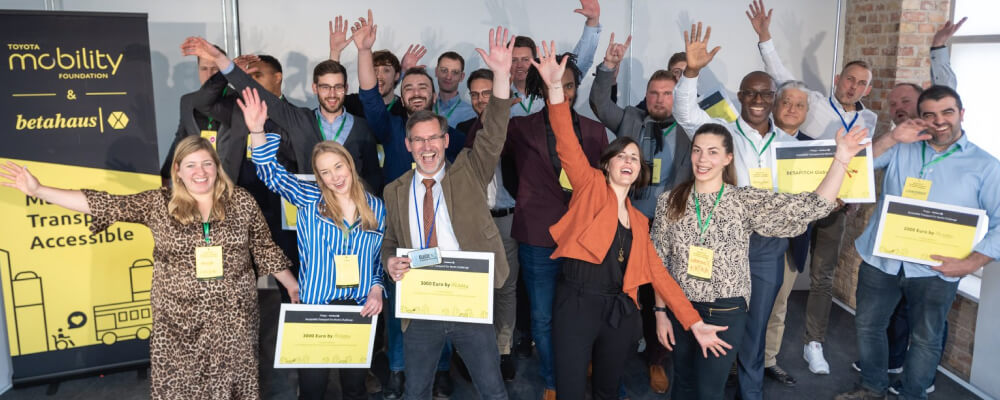 Group photo from the Accessible Transport for Berlin Challenge featuring 12 participating teams and event organizers on the stage. Participants are celebrating, everyone is smiling and waving their hands.