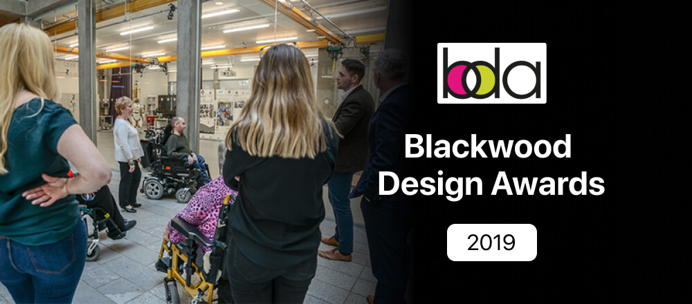 """Image of people touring the Bayes Centre at the University of Edinburgh, where the Blackwood Design Awards Judging Ceremony was taking place. On the right side of the image is written """"Blackwood Design Awards 2019""""."""