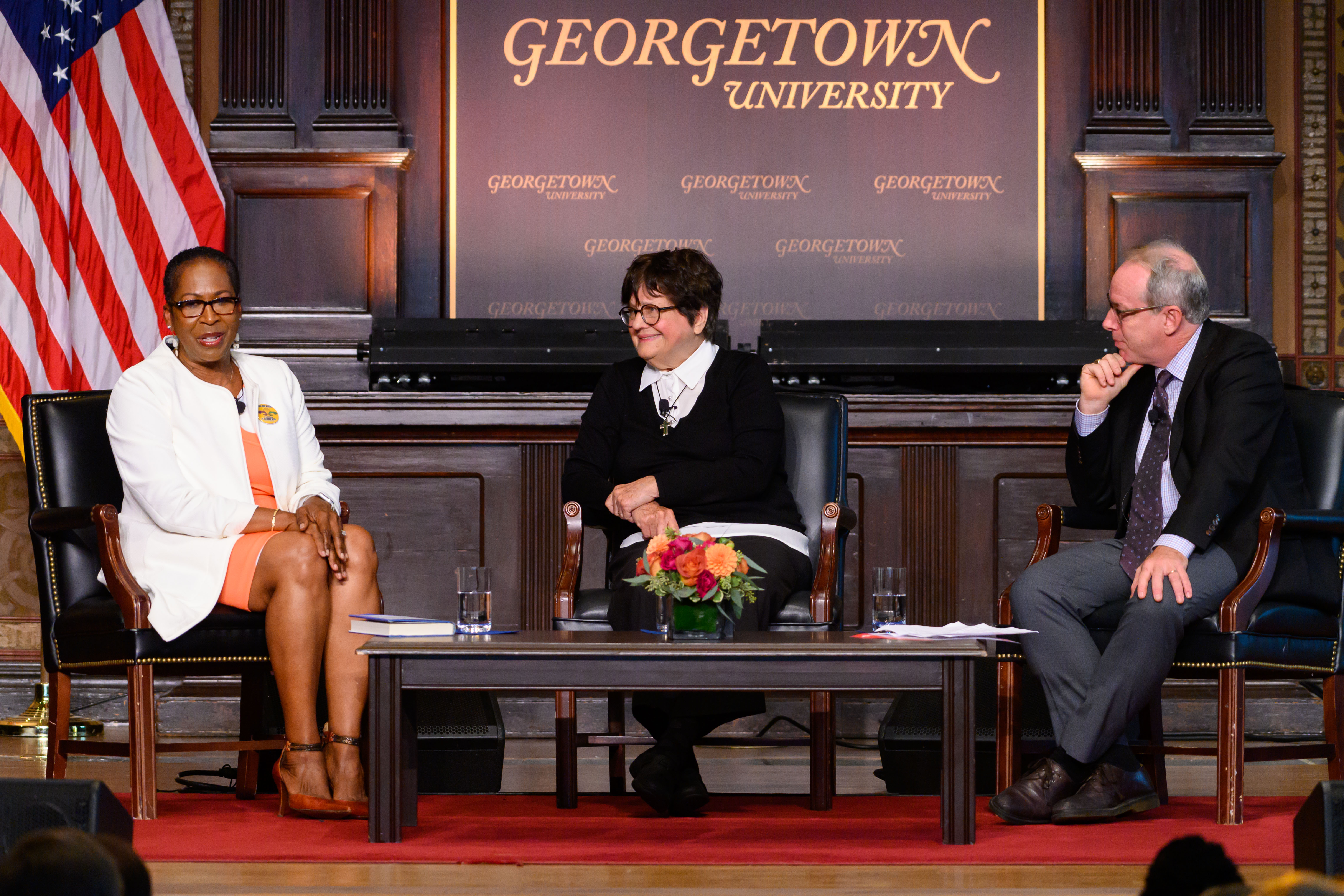 Cheryllyn Branche, Sister Helen Prejean, and Paul Elie converse in Gaston Hall.