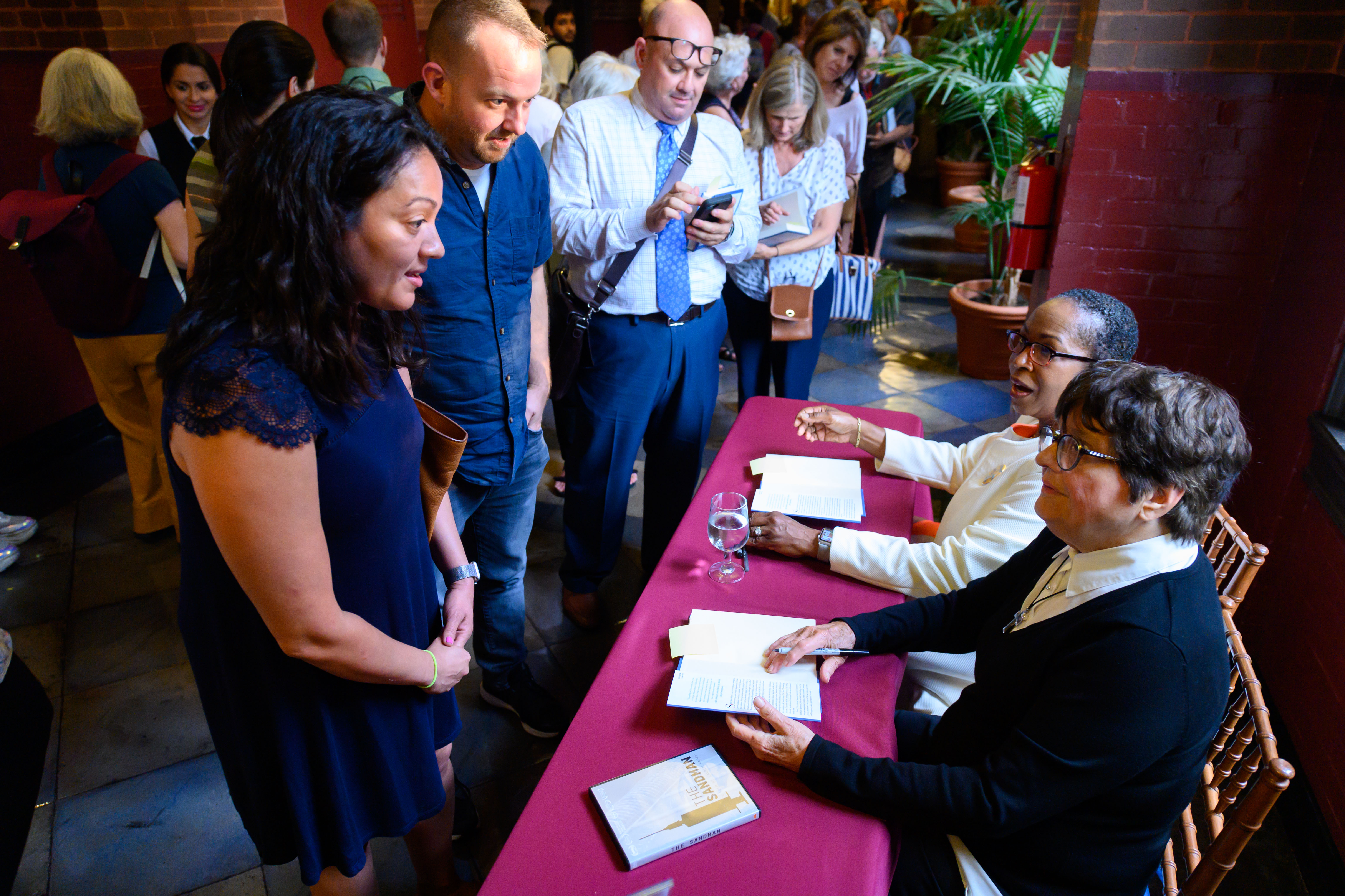 Sister Prejean and Cheryllyn Branche sign books after the event.