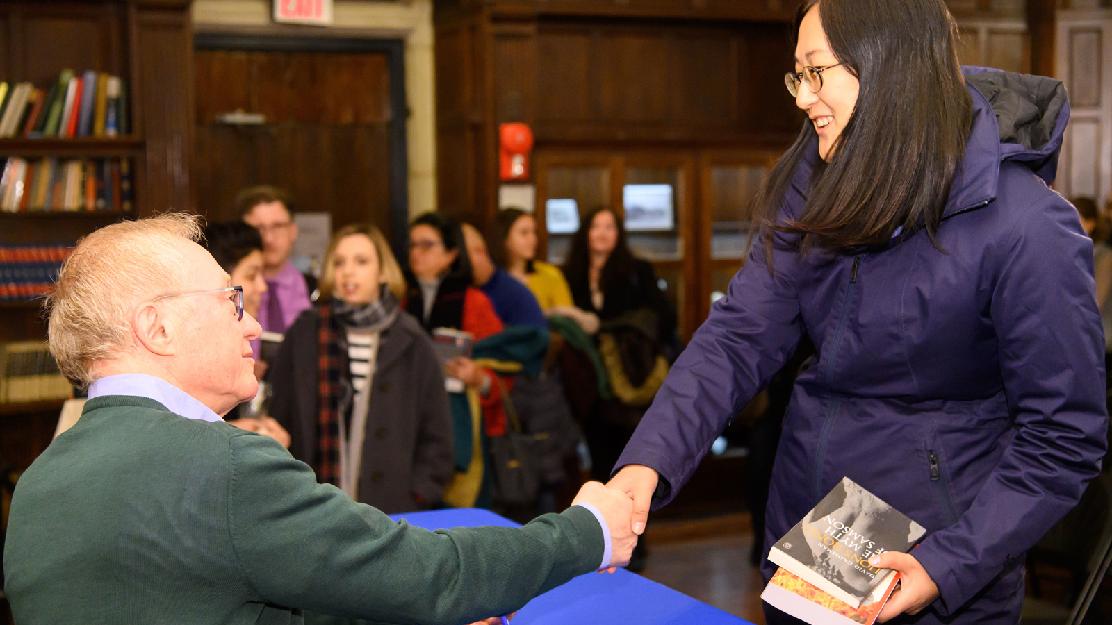 An audience member has books signed by David Grossman.