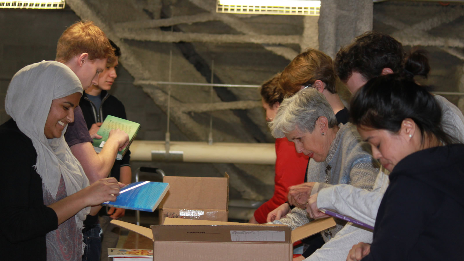 Students and Staff Sort Books Collected Through an Interfaith Book Drive