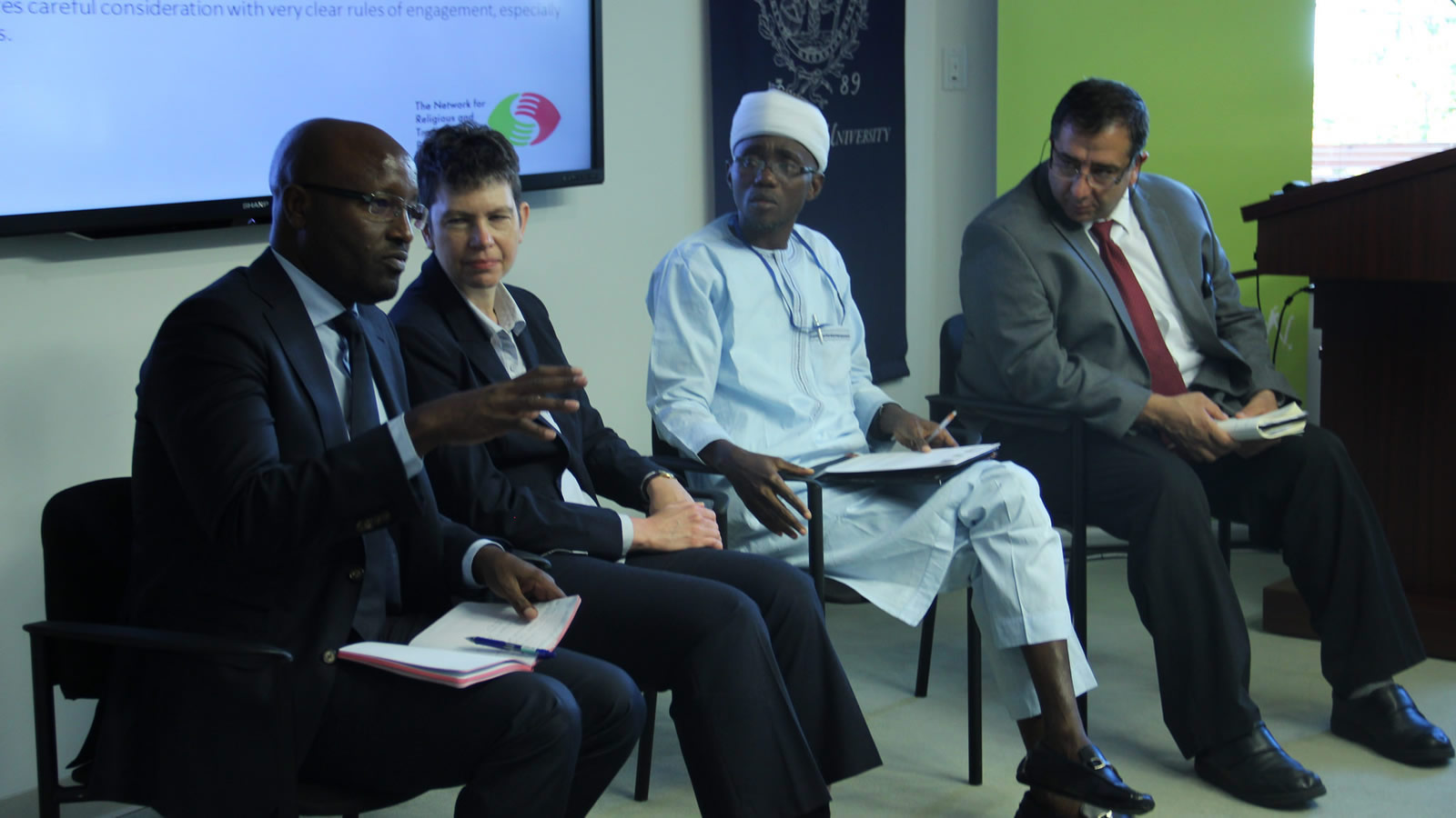 Other panelists listen to Mahdi Abdile discussing a study of former Boko Haram members.