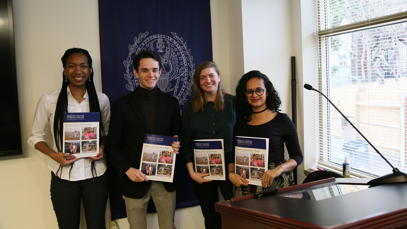 Khaliyah Legette, Jonathan Thrall, Carolyn Vilter, and Mariam Diefallah hold the report featuring their research.
