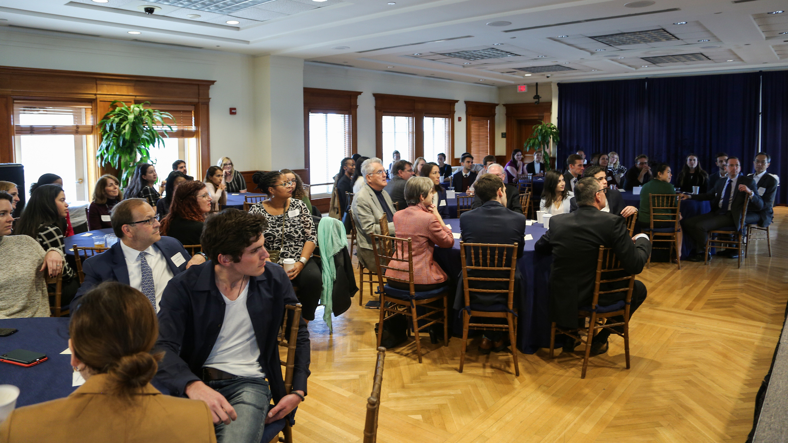 People seated at tables attend the alumni network launch for Religion and the Work of a Lawyer
