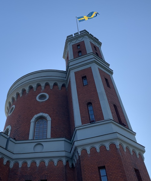 Kastellet, a castle on the island of Kastellholmen in Stockholm. The castle proudly flies the Swedish flag, a symbol of welfare and equality.