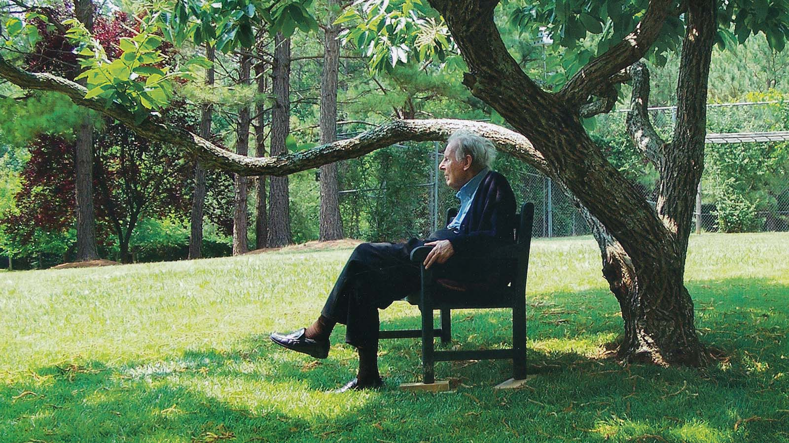 Thomas Berry sits under a tree. Photo courtesy of Mary Evelyn Tucker and John Grim, taken by Marnie Muller.