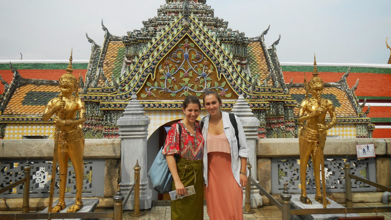 Two Students in Front of Asian Pagoda with Golden Statues