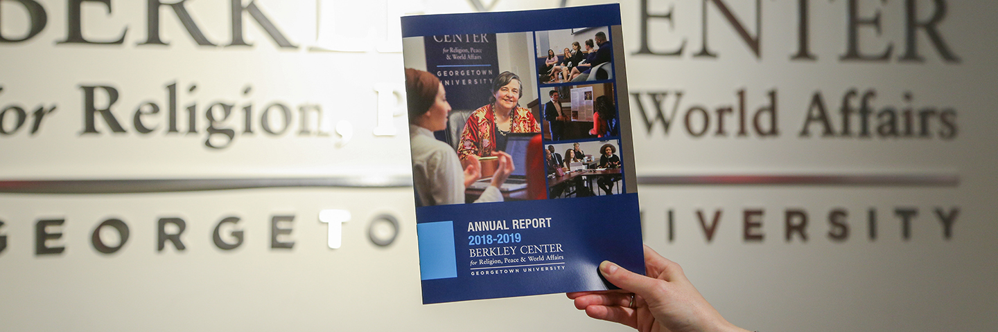 Berkley Center annual report in front of a Berkley Center wall sign