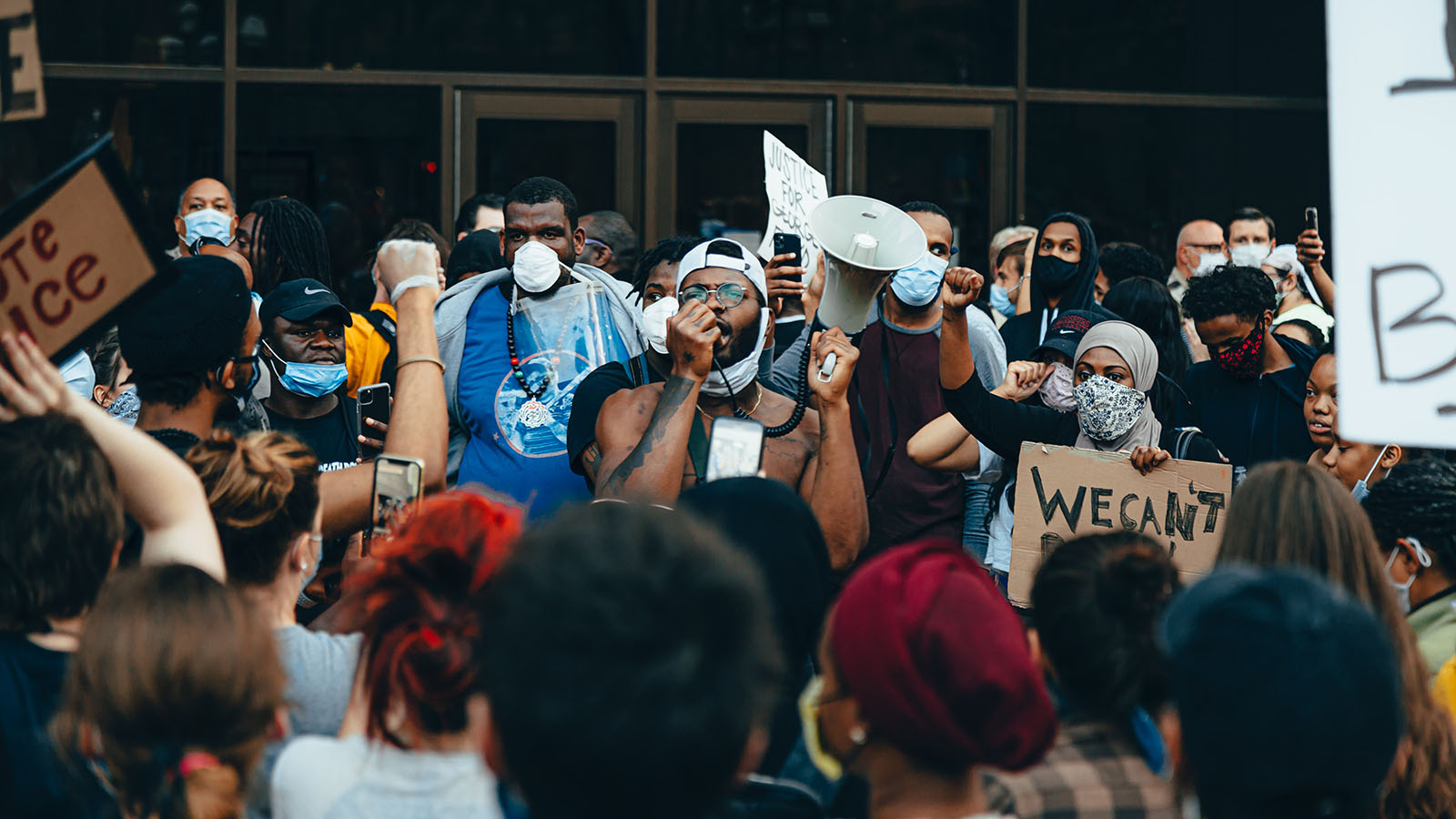 Activist for racial justice surrounded by protesters with protective masks and signs.