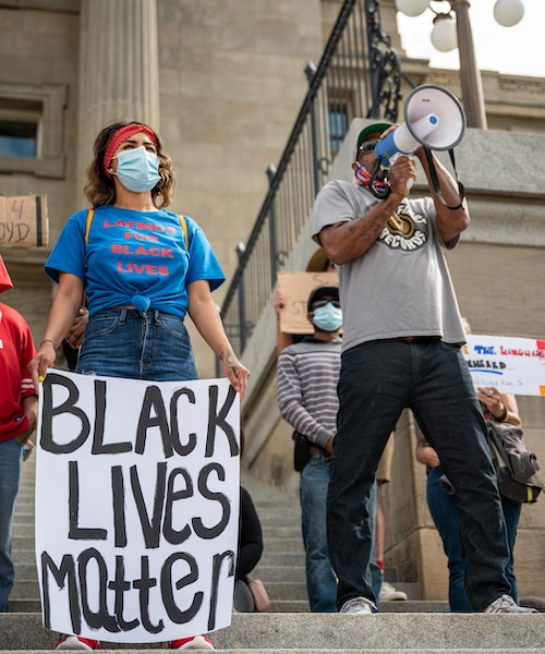 "Woman holding ""Black Lives Matter"" sign stands next to man with megaphone"