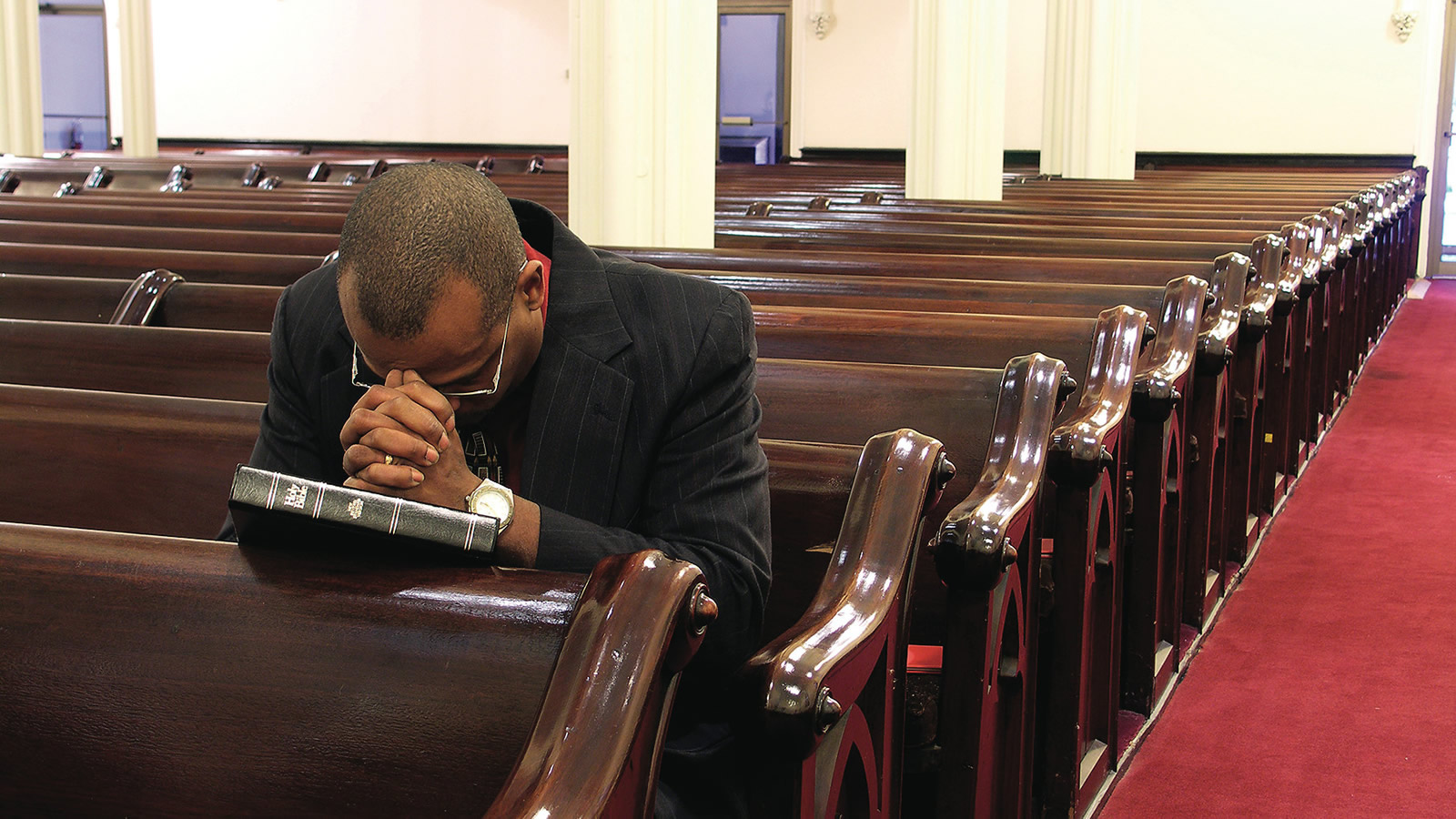Black Man Praying in Church Pews