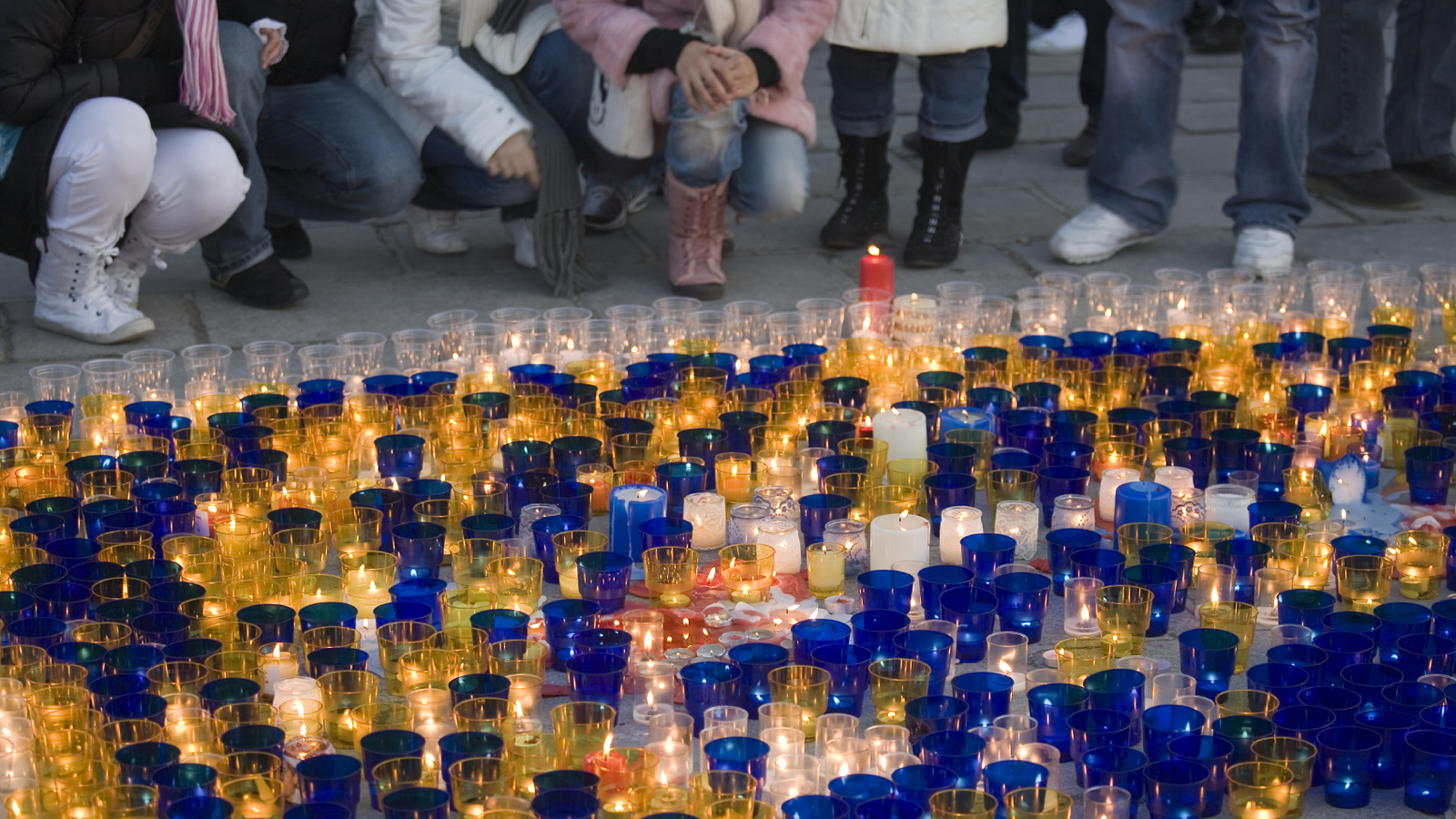 People Kneeling by Blue, Yellow, and White Votive Candles