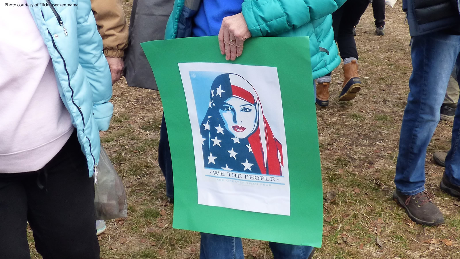 Women's March protester holding an American flag hijab poster