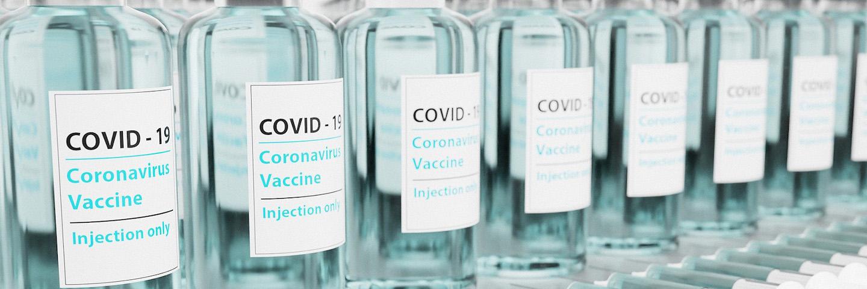 A row of glass COVID-19 vaccine vials