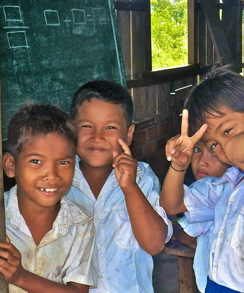 Cambodian students smiling in front of a chalkboard