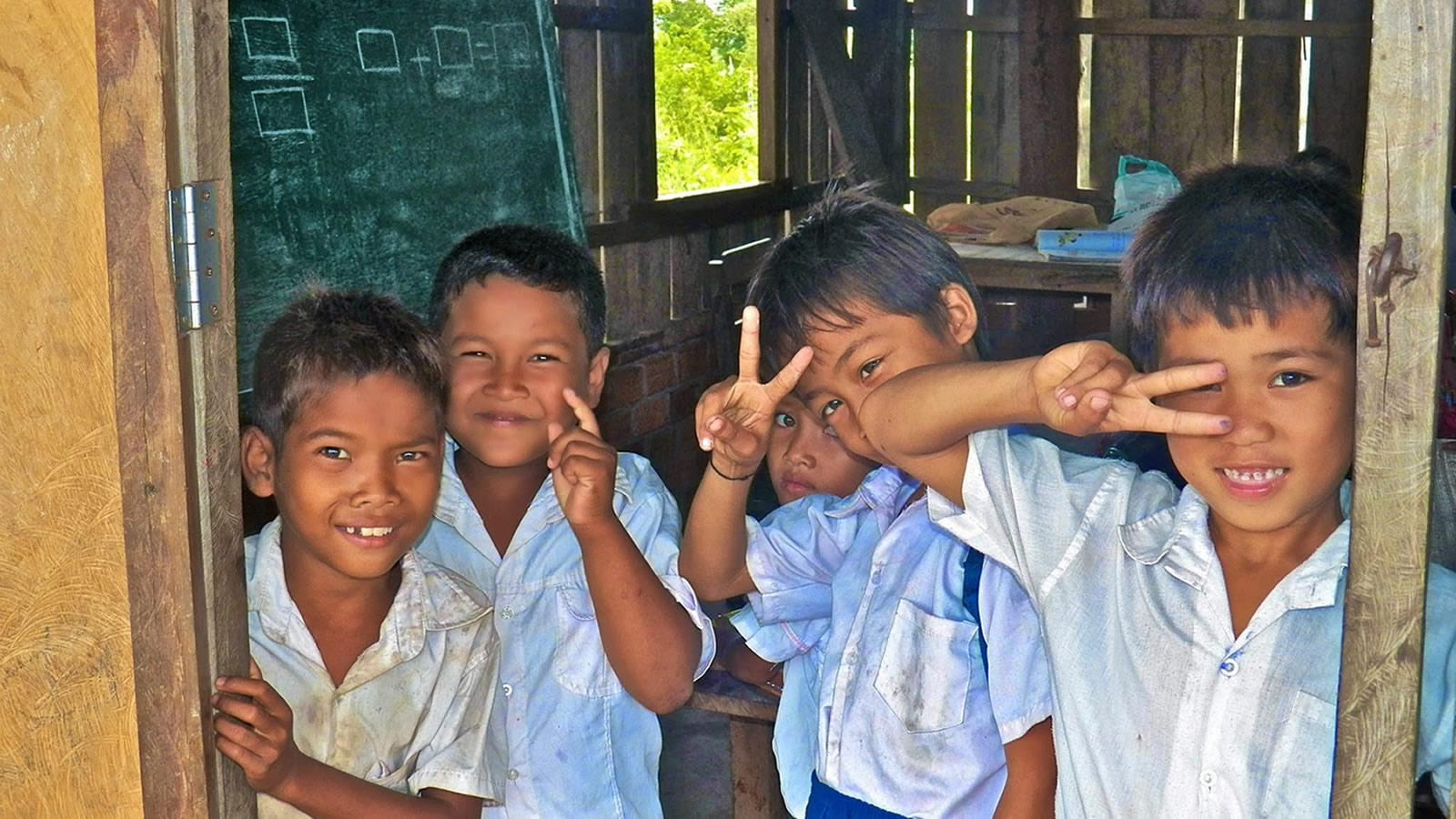 Cambodian Schoolchildren Smiling in Front of a Chalkboard