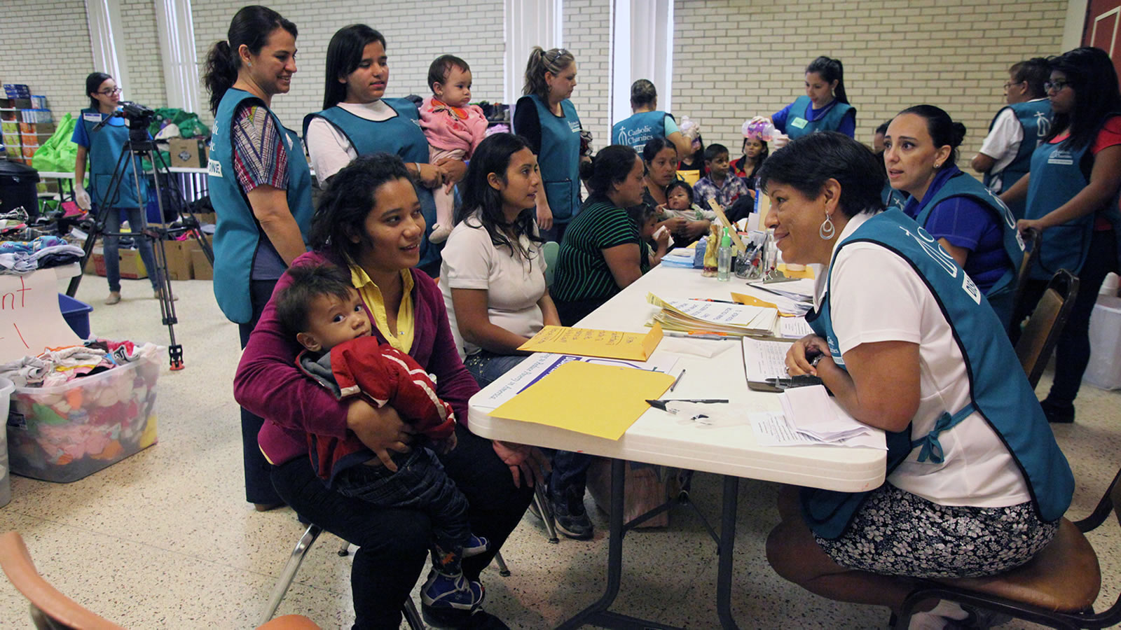 Catholic Charities Disaster Response Team Talks to Central American Refugee Mother and Child in McAllen, Texas