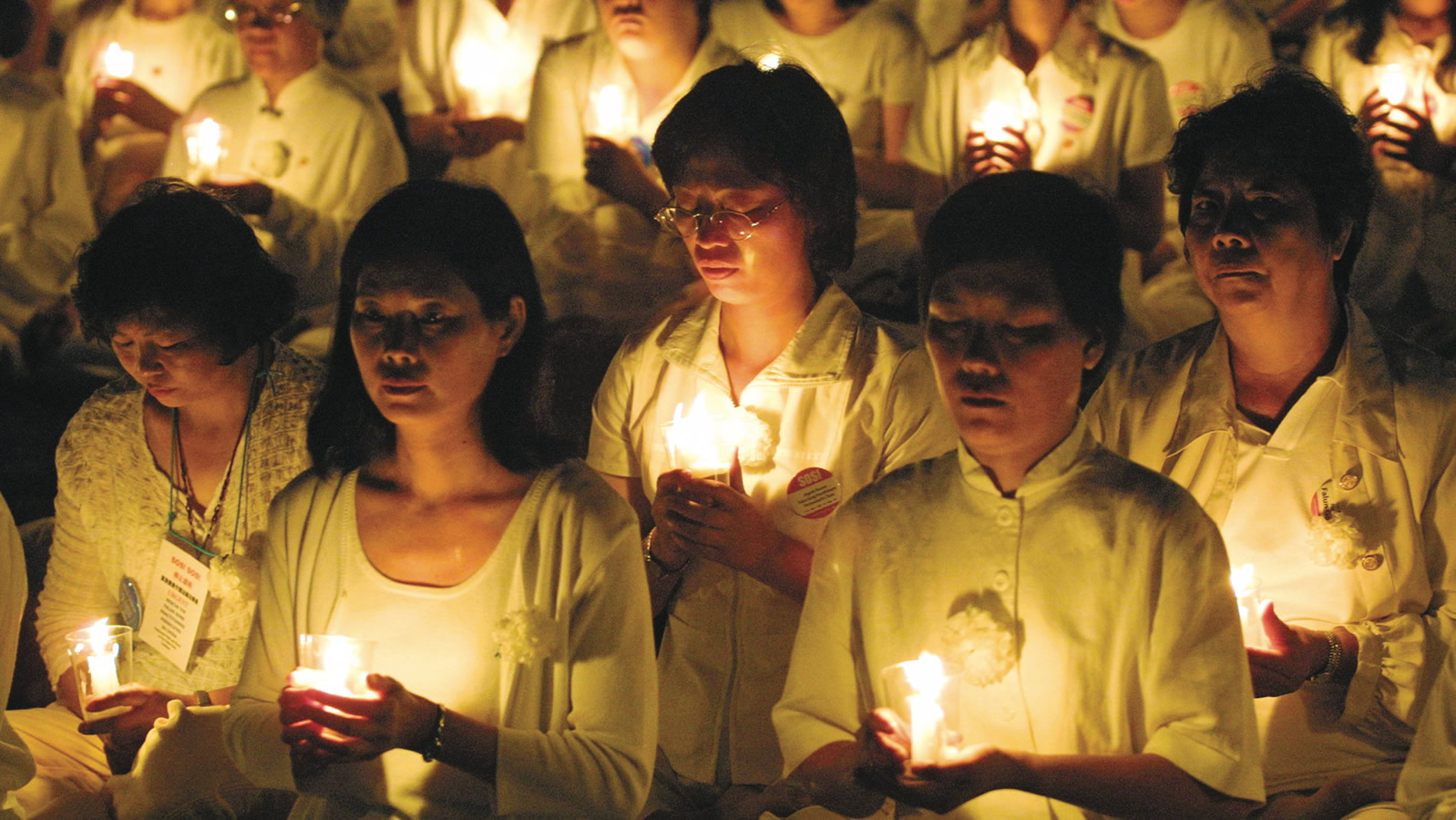 Chinese Women Wearing White and Holding Candles
