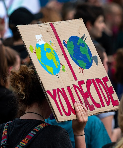 A woman holds a sign in a climate change protest