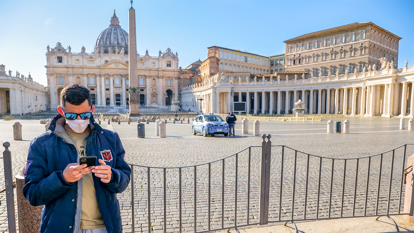 A tourist protected by a medical mask in the square of St. Peter's Basilica, closed to visitors due to COVID-19.