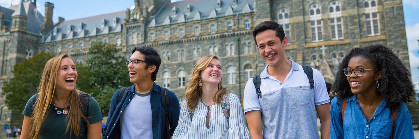 A group of Georgetown student laughing in front of Healy Hall