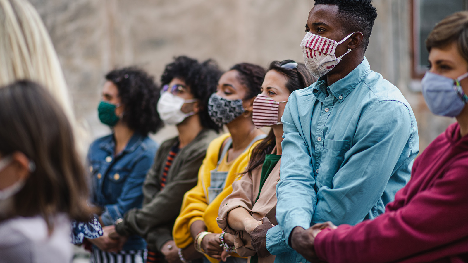 A diverse group of protestors link arms and wear masks to protect against COVID-19